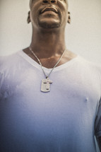 Man in wet t-shirt with a silver cross pendant.