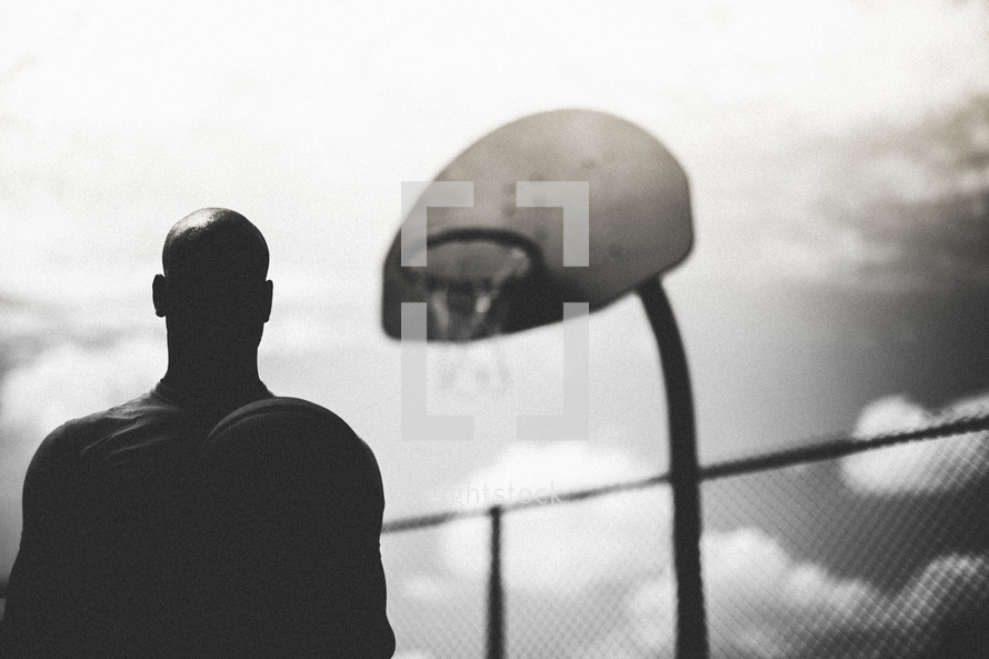 Silhouette of a man standing standing below a basketball hoop.