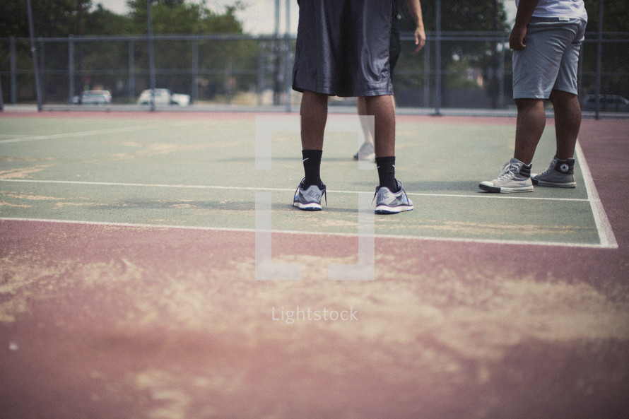 Men's legs on a basketball court.