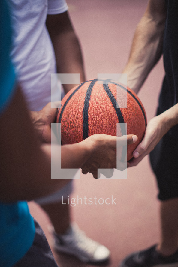 Player's hands holding a basketball.