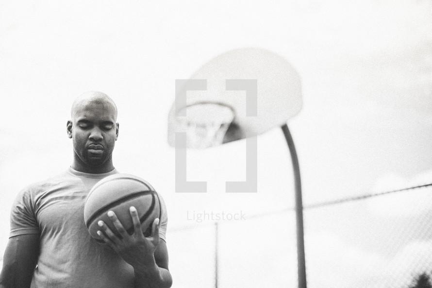Man in prayer on a basketball court.