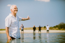 Man standing in the ocean water with friends on the shore.