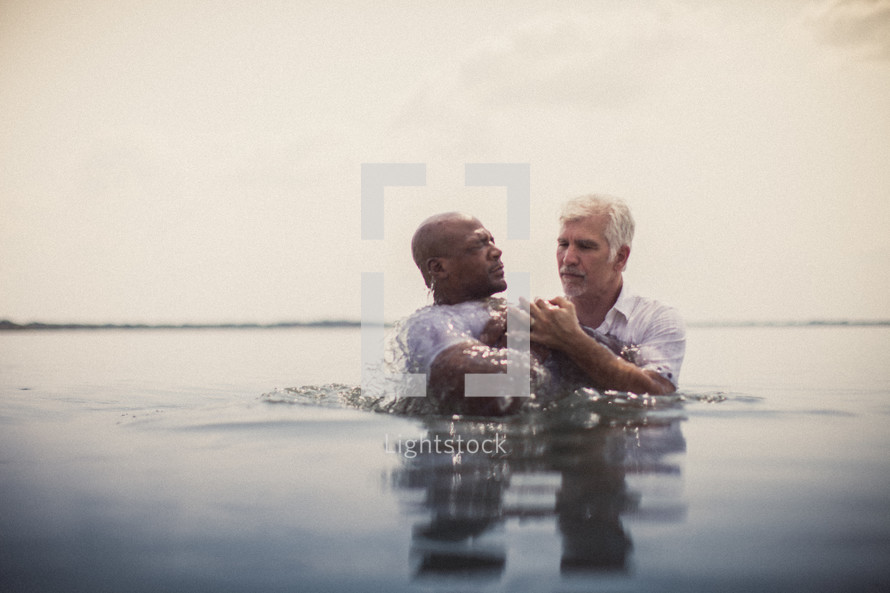 Man being baptized in the ocean water.