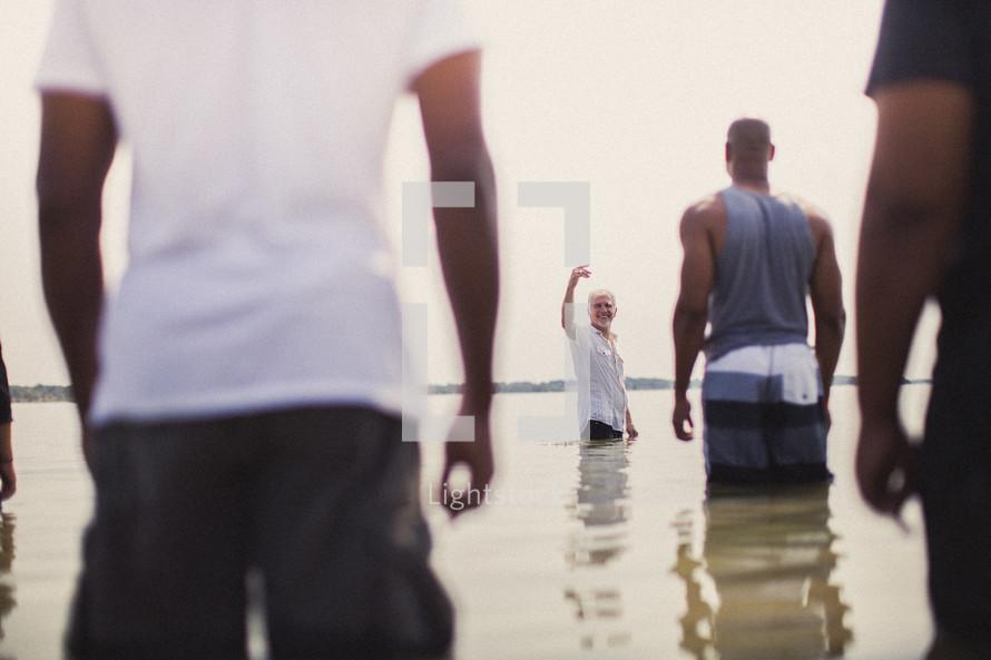 Men standing in the ocean water.