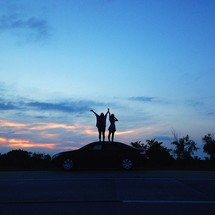 Two people stand on top of a car at dusk with arms raised to the sky.