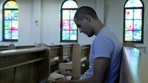 a man reading a Bible sitting in a church