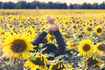Girl reaching hands in a flower field