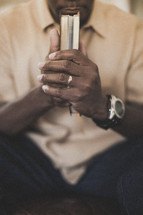 Man praying with Bible in hands.