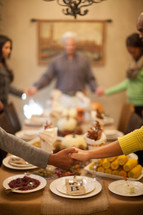 family holding hands in prayer around a Thanksgiving dinner table