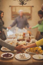 family holding hands around a dinner table