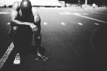 Man kneeling in prayer on a football field.