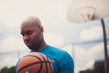 Man in prayer on a basketball court holding a basketball.