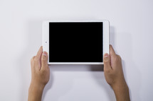 hands holding up a tablet