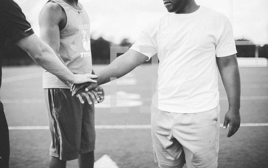 men praying on a football field
