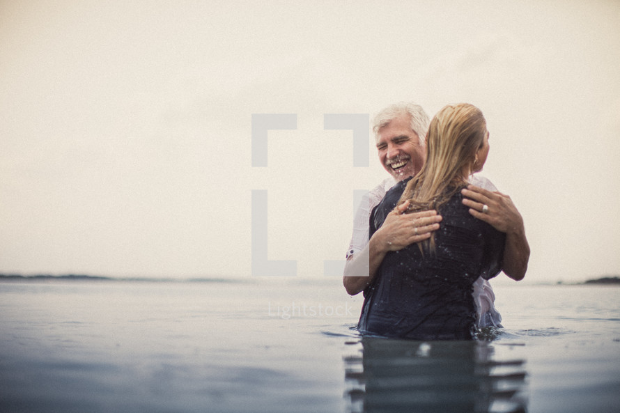 A pastor hugging a young woman after being baptized.
