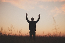 man with his hands raised in worship to God