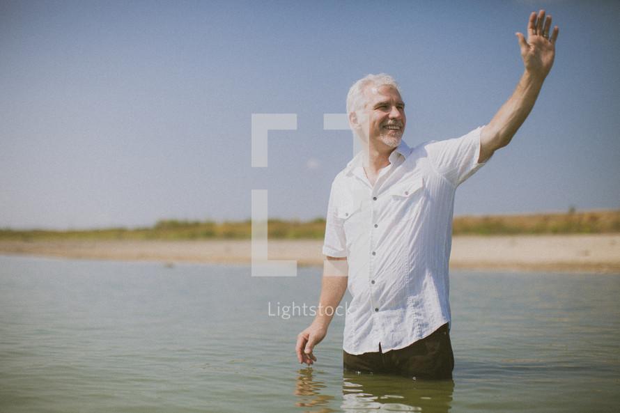 man standing in water waving