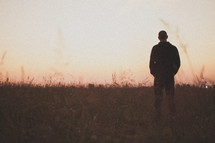 man with his hands in his pockets standing in a field at dusk