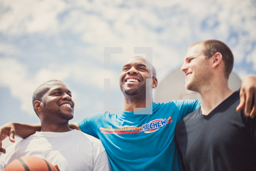 Three smiling men with a basketball.