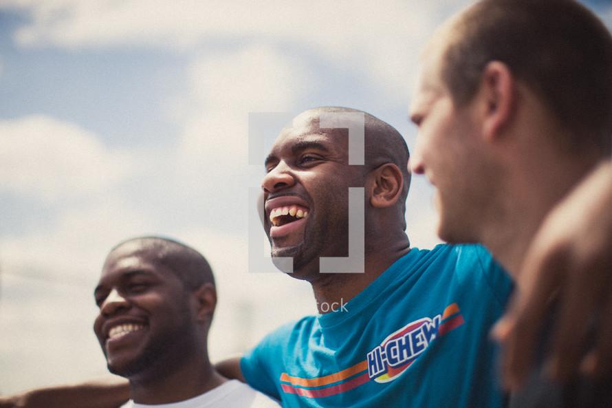 Smiling men in a huddle.