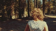Young girl walks through the woods as camera pans up towards trees