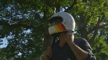 motorcyclist putting on sunglasses and helmet