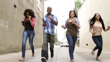 young adults running in an alley carrying cellphones