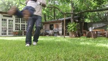 A father swings his son around and around in the back yard.