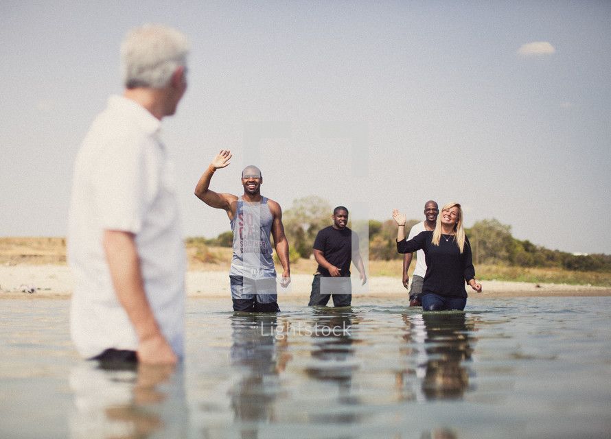 Friends standing in the ocean water.