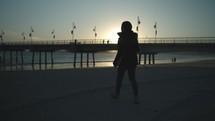 Girl walking towards pier at sunset.