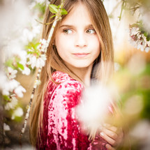 face of a little girl through spring branches