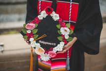 a female holding a graduation cap