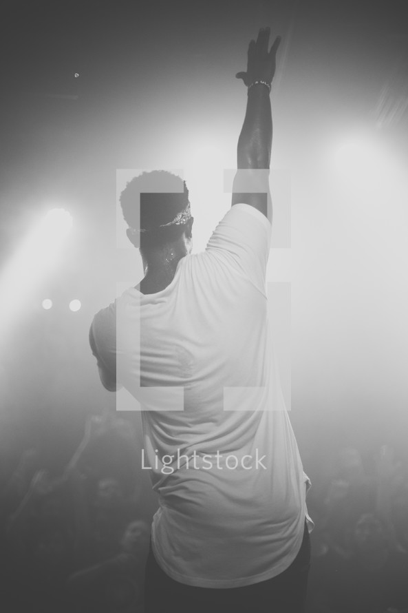 man on stage with a raised hand
