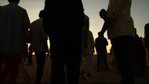 silhouettes of men and women gathering at sunset