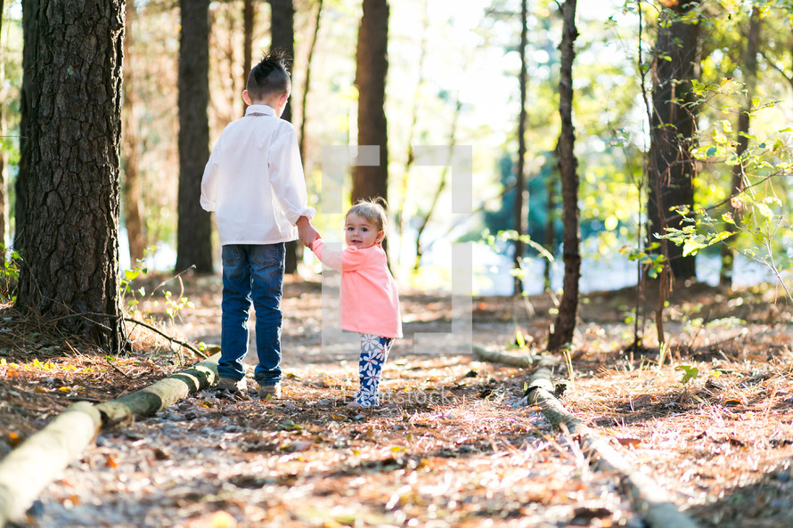 brother and sister holding hands walking on a path outdoors