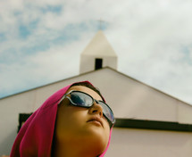 Woman With Pink Headcloth and Church in Background