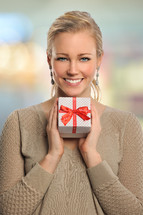 a smiling woman holding a wrapped gift