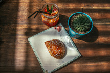 croissant and ice tea on a wood table