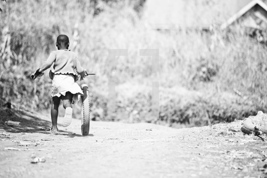 Little African girl running with bike wheel