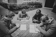 a group of men in a prayer circle during a Bible study
