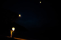 man releasing paper lanterns into the night sky
