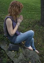 Teen girl holding cross, praying with Bible on fallen tree in park.