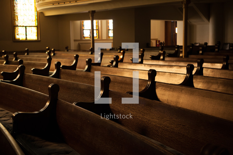 A church sanctuary filled with wooden pews.