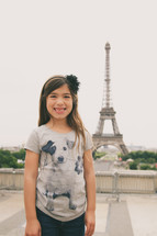 a little girl standing in front of the Eiffel Tower
