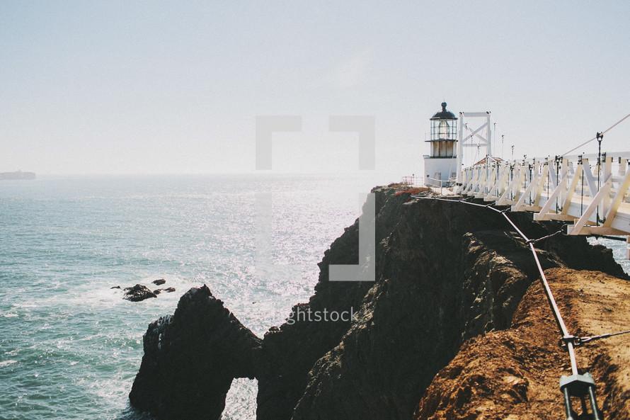 swinging bridge leading to a lighthouse