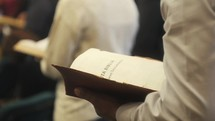 parishioners turning pages of Spanish Bibles during a worship service