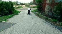 man walking alone near abandoned buildings