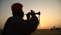 silhouette of a man playing a horn