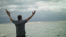 a man standing on a beach holding a Bible with hands raised in prayer