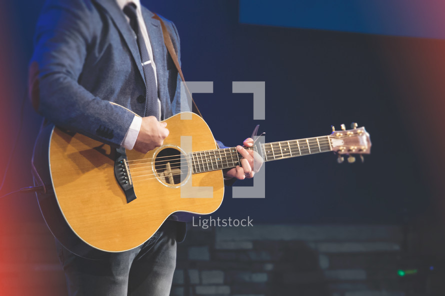 Worship leader in suit with an acoustic guitar